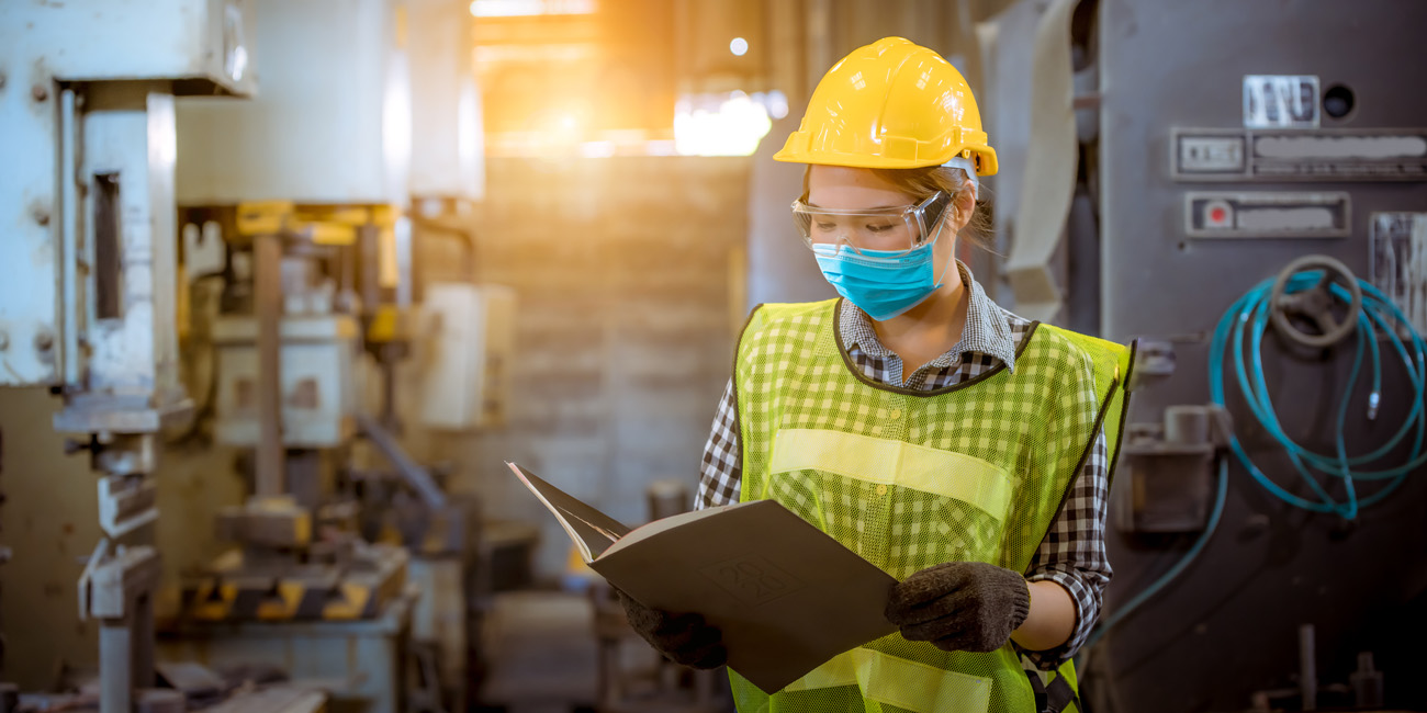 Female factory worker taking worksite safety seriously as she wears her hardhat, goggles and mask